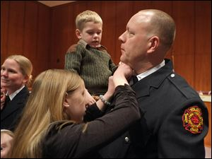 Jeff Schroeder, holding son Jake 3, gets new collar brass from his daughter Sophia, after he was promoted from private to lieutenant.
