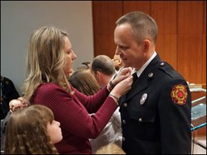 John Schnorberger gets new collar brass from his wife Amy after being promoted from lieutenant to captain. Looking on are their children, Katy, 9, and Drew, 7.