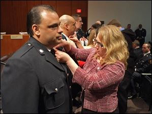 Lynn Rodriguez pins new collar brass on the shirt of her husband, newly promoted Toledo Fire and Rescue Battalion Chief David Rodriguez.
