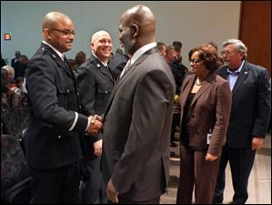 Newly promoted Captain Dexter Baker, left, is congratulated by Toledo Mayor Mike Bell.