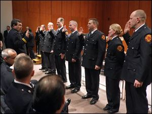 David Dauer Toledo Fire and Rescue Department CFO and battalion chief, left, swears in newly promoted lieutenants.