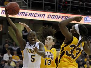 UT's Janelle Reed-Lewis goes up for two over CMU's Jessica Schroll, center, and Brandie Baker.