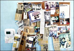 Photos and news clippings adorn a bulletin board at Torio Health Club, detailing the stories and successes of the facility's members over the years, making it as much a museum as a weight room.
