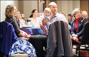 Sian McHale, left, and husband, Aaron, holding 4-month-old son Silas, listen to speakers during the Greater Toledo Right to Life fifth annual Legislative Briefing Breakfast at The Premier banquet hall in Toledo.