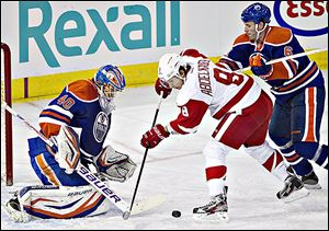The Red Wings' Justin Abdelkader, center, is stopped by Edmonton Oilers goalie Devan Dubnyk.