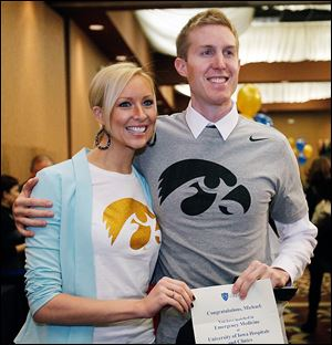 Anna Haarstad, 28, left, and her husband, Michael, 31, show off their Hawkeye T-shirts in celebration of his acceptance to his first-choice residency, emergency medicine at the University of Iowa.