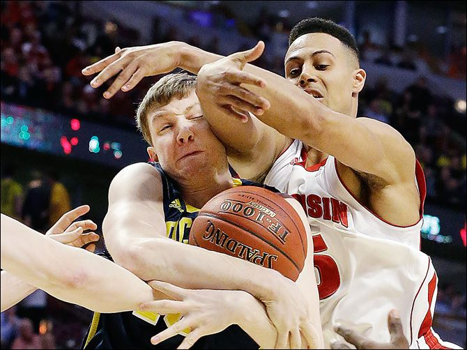 Michigan's Matt Vogrich grabs a rebound in front of Wisconsin's Ryan Evans, right, during the first half of a game at the Big Ten tournament Friday.