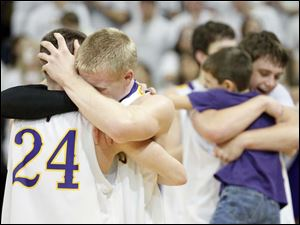Leipsic High School players Aric Schroeder ,24, and Austin Barerra, 10, celebrate with teammates after beating Ottawa Hills.