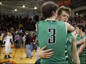 Ottawa Hills High School player Geoff Beans, 3, consoles teammate Lucas Janowicz, 35, after the Green Bears lose to Leipsic High School.