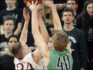 Ottawa Hills High School player RJ Coil, 40, blocks the shot of Leipsic High School player Aric Schroeder, 24.
