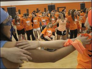 Susan Hagemeyer, 16, center, clasps an arm around a fellow orange Air Force teammate while dancing.