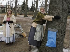 Annie Doerr, left, laughs as her fellow volunteer Colleen Nagel jokingly demonstrates the width of a Maple tree that is sufficient to tap it for sap.