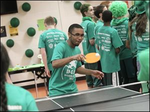 Isaiah Carter, 14, plays ping-pong with his fellow green Army teammates.