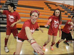 Red Marine team member Lexi Lopez, 17, center left, screams as she and other students dance together.