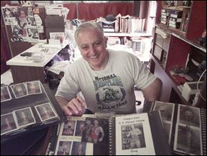 Longtime Toledo fitness  leader and wrestling official Dick Torio goes through scrapbooks from his years of weight training men in this June 1999 photo.
