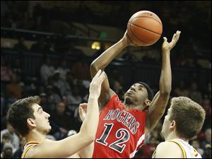Rogers' Clemmye Owens takes a shot as he is guarded by Brecksville-Broadville Heights' Tommy Tupa (10) and Mark Chrzanowski (11).