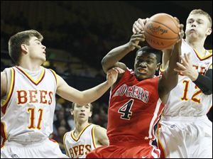 Rogers' Keandre Gilmer (4) pulls in a rebound against  Brecksville-Broadville Heights' Mark Chrzanowski (11)  and Matt Csuhran (12).