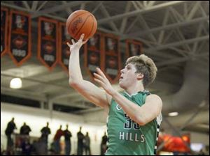 Ottawa Hills High School player Lucas Janowicz, 35, shoots against Leipsic High School player Aric Schroeder, 24.