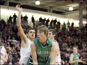 Ottawa Hills High School player RJ Coil, 40, looks to drive against Leipsic High School player Caleb Barerra, 14.