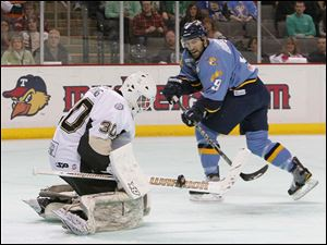 Toledo Walleye player Aaron Bogosian, 9, has his short handed goal attempt stopped by Wheeling Nailers goalie Scott Darling.