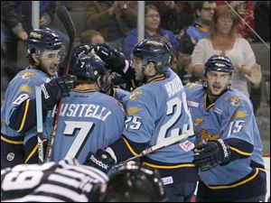Toledo Walleye players Trevor Parkes, 8, nino Musitelli, 7, Ben Youds, 25, and Willie Coetzee, 15, celebrate a goal by Parkes.