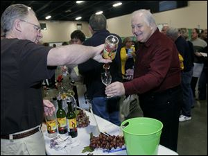 It's Your Winery's Dave Foltz pours Toledoan Bill McDaniel a sample.