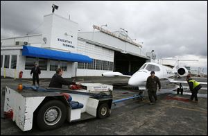 Todd Smolinski pulls a plane out of the hangar at National Flight Services in Swanton.  Business at National Flight Services has decreased by 25 percent to 30 percent since 2003, but things are looking up.