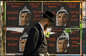 An Ultra Orthodox Jewish man walks past posters depicting US President Barack Obama wearing a traditional Arab headdress, in Jerusalem in 2009.