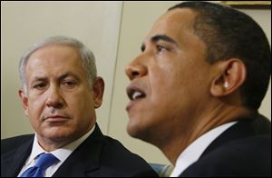 Israeli Prime Minister Benjamin Netanyahu, right, looks towards President Barack Obama as he speaks to reporters in the Oval Office of the White House in Washington.