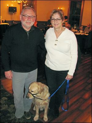 Frank Booth and Gale Tedhams with Murphy, an assistance dog in training.