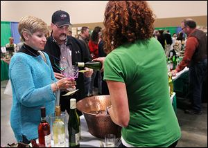 Michigan residents Valarie Cerasuolo and Craig Baker sample Firelands Winery wine poured by Melissa Kadow during the Glass City Wine Festival.