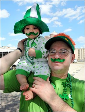 John Palenzuela of Webster, Texas holds his son, Kayden, 6 months old, as they watch the Houston St. Patrick's Day Parade in downtown Houston, Texas Saturday.