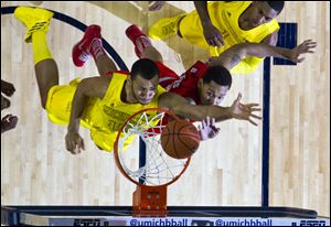 Michigan forward Jon Horford, left, drives to the basket while defended by Ohio State center Amir Williams during their Feb. 5 game at Crisler Center in Ann Arbor. The Buckeyes are a No. 2 seed in the NCAA tournament, while the Wolverines are a No. 4 seed. Both will open the tournament this week in their home states.
