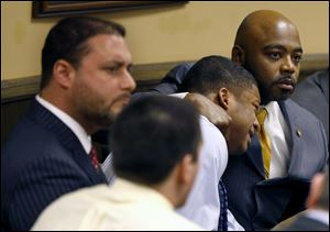 Defense attorney Walter Madison, right, holds his client, 16-year-old Ma'lik Richmond, second from right, while defense attorney Adam Nemann, left, sits with his client Trent Mays, foreground, 17, as Judge Thomas Lipps pronounces them both delinquent on rape and other charges after their trial in juvenile court in Steubenville, Ohio.