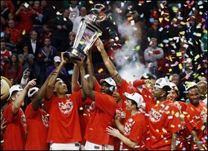 Ohio State players celebrate after winning an NCAA college basketball game against Wisconsin in the championship of the Big Ten tournament. Ohio State won 50-43.