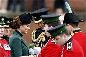 Britain's Kate Duchess of Cambridge, third left, stands with her husband Prince William, fourth left, before presenting traditional sprigs of shamrock to members of the 1st Battalion Irish Guards at the St Patrick's Day Parade at Mons Barracks in Aldershot, England.