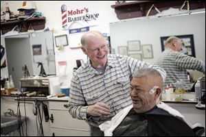 Harold Mohr prepares to shave around the ears of Ray Garcia at Mr. Mohr's barber shop on South Lane Street in Blissfield. The barber has been cutting hair 50 years, following successful completion of training at a barbers' college in Detroit.