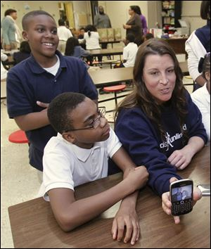 Heidi Burkhart shows a photo on her phone to kids at the Kids Unlimited charity office located inside Rosary Cathedral school in Toledo. Near her is Jerome Morgan, standing, and Brian Staples.