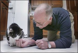 Joe Reynolds on occasion will get down on his hands and knees to feed Kit Kat, who is suffering from kidney disease but is being treated with fluids.