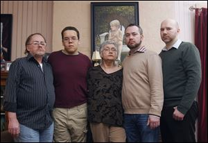 John Schroeder, left, Shawn Schroeder, Sandra Schroeder, Christopher Schroeder, and his partner, Adrian Lilly, pose in front of a painted portrait of Matthew Schroeder, who died of a heroin overdose at his bedroom desk in the Old West End. John and Sandra are Matthew's parents, and Shawn and Christopher are brothers.