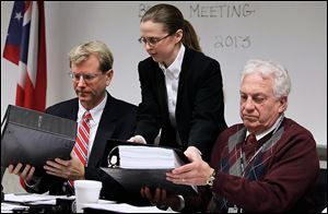Meghan Gallagher, director of the Lucas County Board of Elections, hands binders to board member Jon Stainbrook, left, and board chairman Ron Rothenbuhler during the board's meeting.