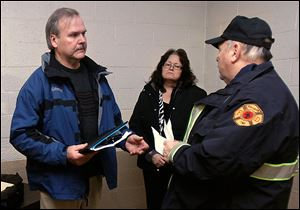 Harold Stanton, left, former fire chief of Jerusalem Township, and his wife, Kathy Stanton, speak to retired firefighter Richard Wilson after Mr. Stanton was fired during a public hearing.