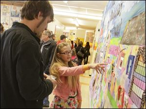 Brad Geiner, of Toledo, left, listens as his daughter Kayla, 10, points out parts of an art piece.