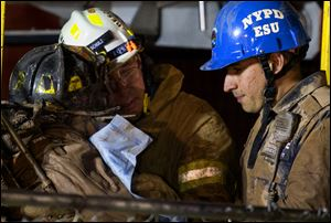 A worker, with black fire helmet at left, is rescued from an MTA subway construction project in New York early today after being trapped up to his chest in debris for several hours.