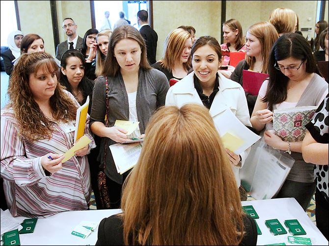 BIZ jobfair21p University of Toledo nursing student Marisela Lemus, center right, poses a question to ProMedica human resources specialist Sharon Dachenhaus Wednesday afternoon during the University of Toledo's job fair for nursing students at the Hotel on the university's Health Science Campus in South Toledo. This was the 13 the university had solely hosted the job fair Featuring 26 vendors, organizers said they were expecting more than 100 recent and upcoming graduates from the University of Toledo, Bowling Green and other programs in the area to attend.   THE BLADE/KATIE RAUSCH