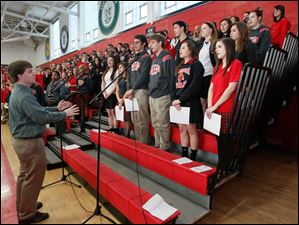 The Cardinal Stritch High School Chorale, under the direction of Tyler Lentz, left, performs the 'Star-Spangled Banner.'