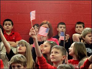 Jeremiah Duvall, center holding flag up, and other second graders welcome the new citizens during the naturalization ceremony.