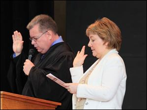 U.S. District Court Judge James R. Knepp, reads the Oath of Citizenship, and citizen Mariana Steffan, originally from Russia, takes the oath with the other soon-to-be-citizens.