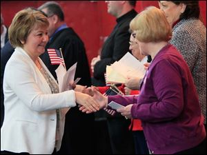 Mariana Steffan, originally of Russia, is welcomed as a U.S. citizen by Chris Burkhart, Fort Industry NSDAR Chapter.