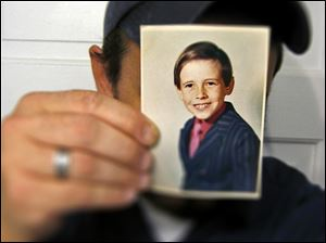 An image of Allen when he was young held in front of his face.